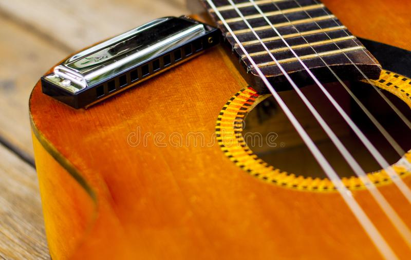 A harmonica on a classical guitar. stock photos