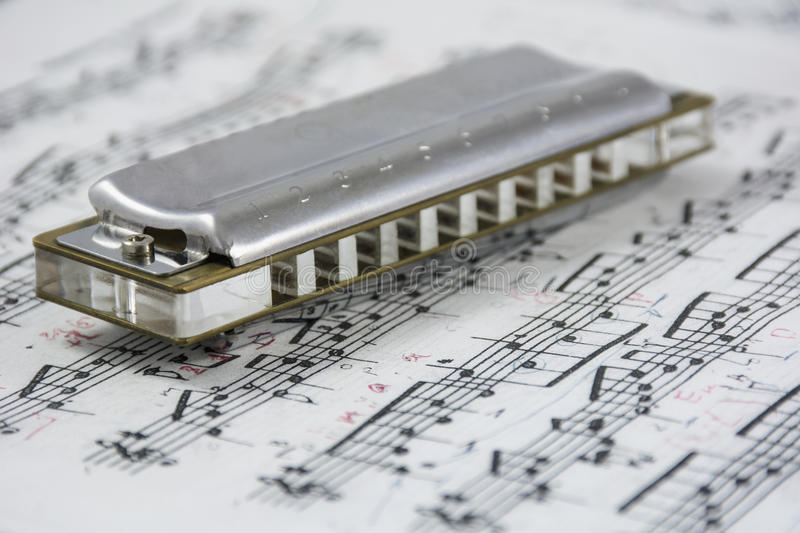 Harmonica is on the musical notes stock photos