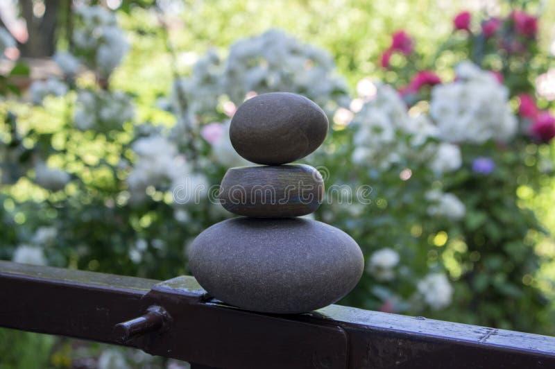 Harmonie et équilibre, cairns, pierres simples d'équilibre dans le jardin, sculpture en zen de roche, cailloux gris-foncé photos libres de droits
