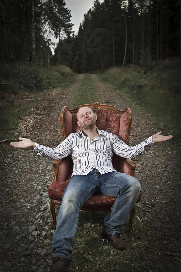 Harmonious and Happy man in the Woods. Sleazy man in a classic vintage chair in the middle of a road in the woods. Smoking cigar and get served Cognac from a royalty free stock photo