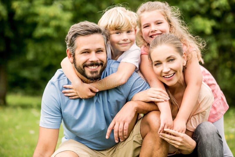 Harmonische Familie mit zwei glücklichen Kindern lizenzfreie stockfotos
