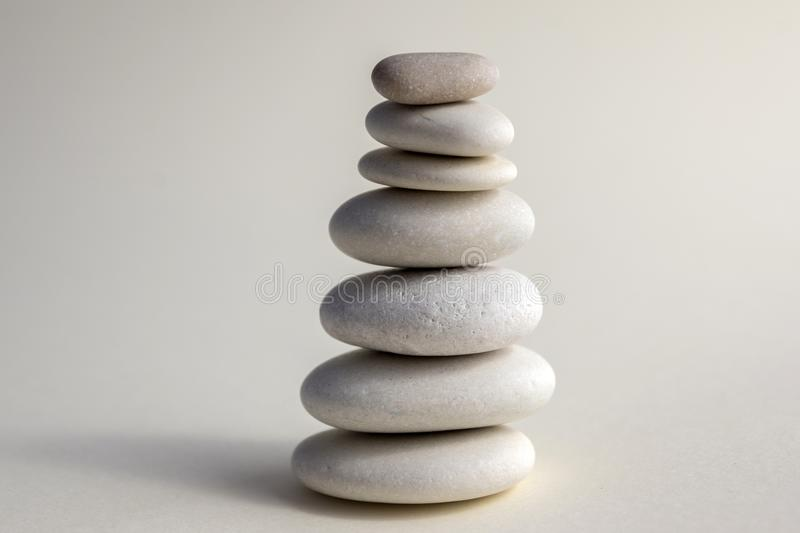 Harmony and balance, cairns, simple poise stones on white background, rock zen sculpture, white pebbles, single tower, simplicit royalty free stock photography