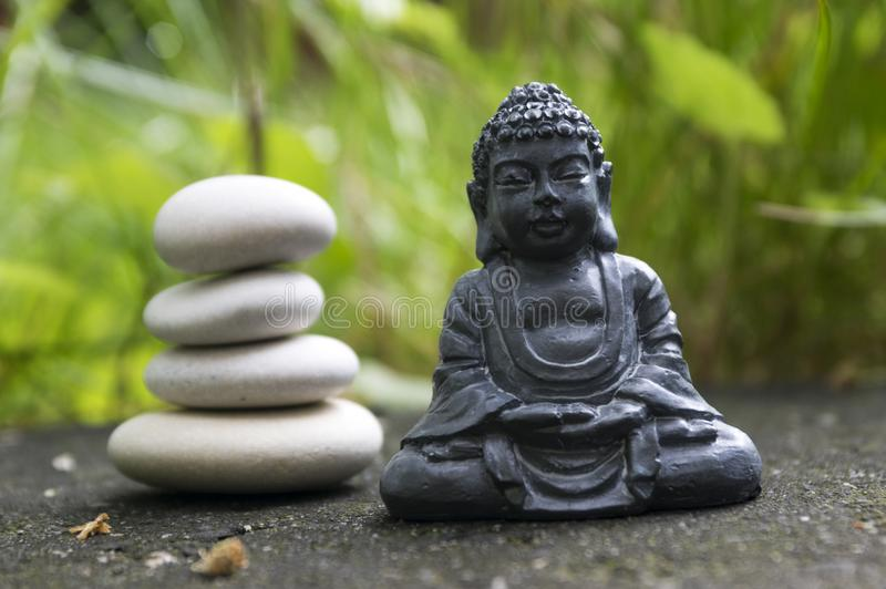 Harmony and balance, dark grey Buddha statuette. Harmony and balance, simple pebbles tower in the grass, simplicity, four stones and dark grey Buddha statuette royalty free stock image