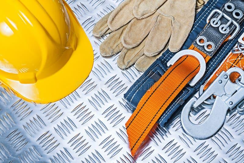 Harnais et gants de sécurité jaunes de casque sur la feuille ondulée de metall photo libre de droits