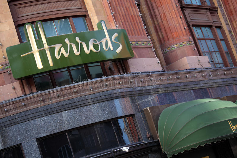 Harrods Department Store Knightsbridge London, sign and logo above building entrance. Illuminated Harrods sign and entrance canopy on the outside wall of the stock photography