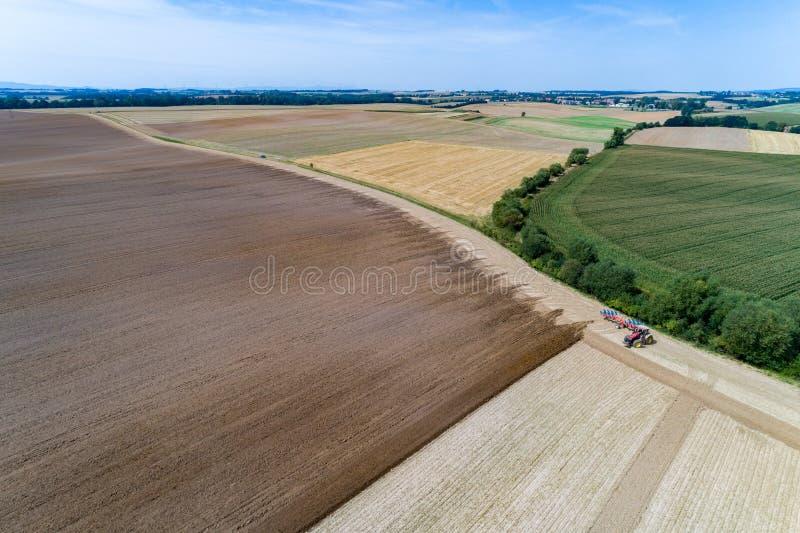 Harrownig de tracteur le grand champ brun photos stock