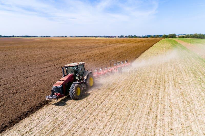 Harrownig de tracteur le grand champ brun image stock