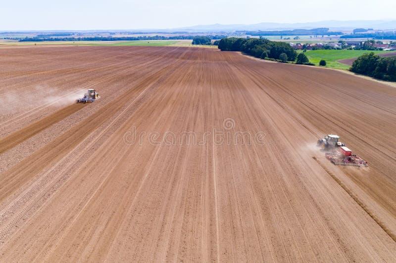Harrownig de tracteurs le grand champ brun images stock