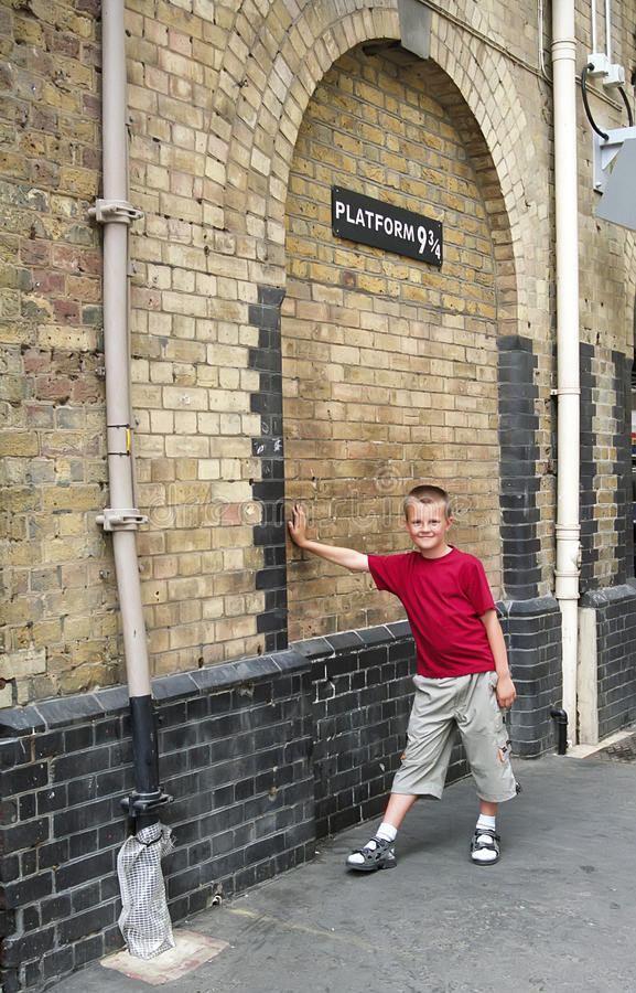 Harry Potter platform in London. Boy leaning against the wall to fantasy Platform 9 3/4 from famous Harry Potter book stock images