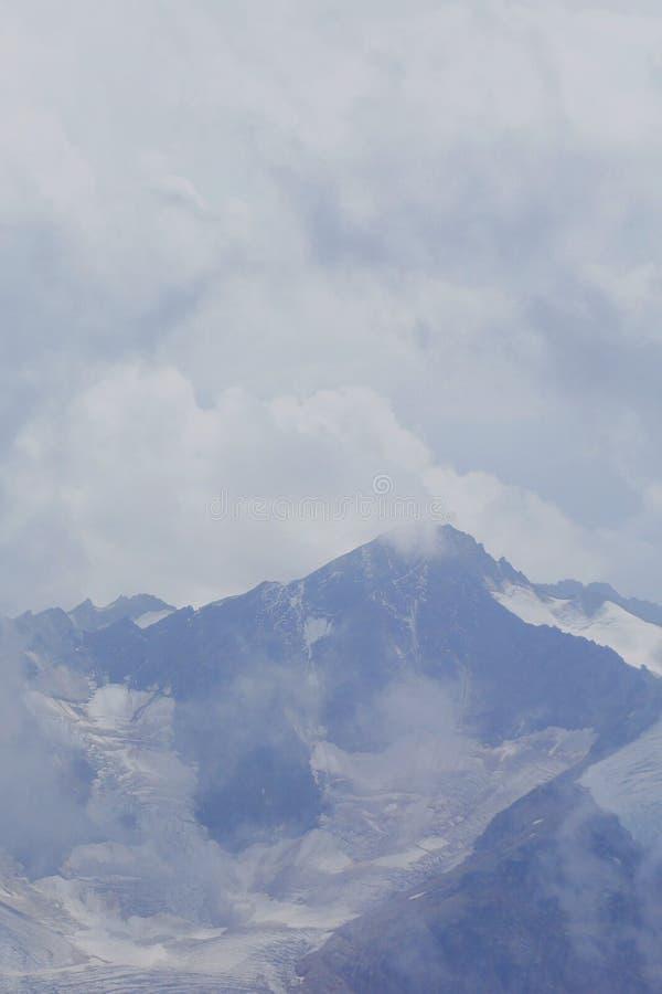Harsh mountain landscape hiding behind cumulus clouds. Blurred photo bokeh stock photo