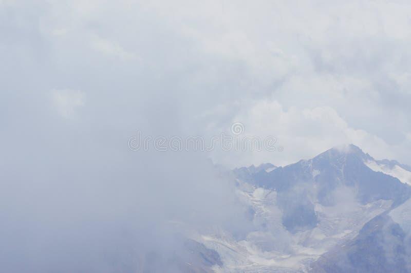Harsh mountain landscape hiding behind cumulus clouds stock photos