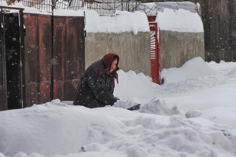 Harsh winter with snow in Bucharest, capital of Romania. Old woman in snow. Siberian frost royalty free stock photography