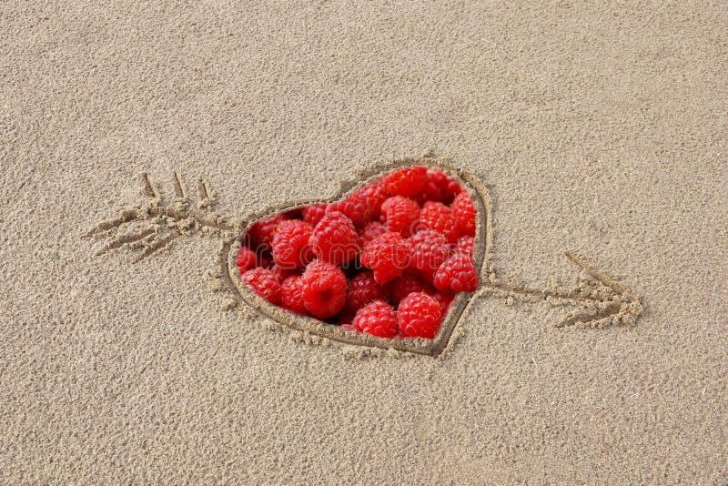 hart door een pijl wordt doordrongen die op het zandstrand trekken binnen r dat stock foto's