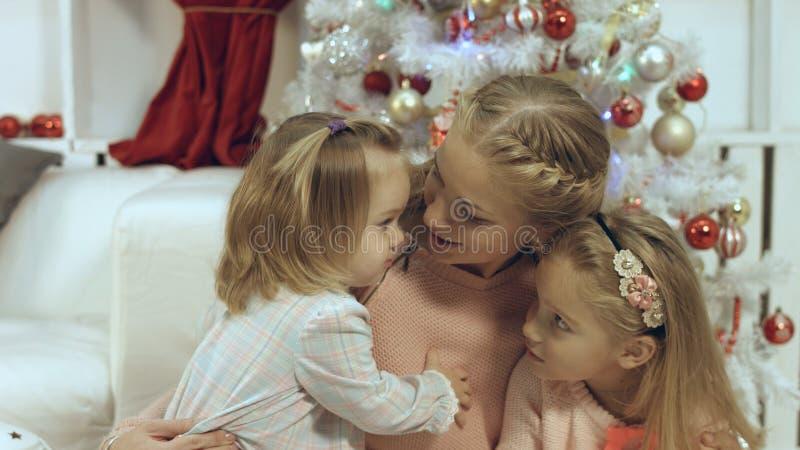Hart-doordringende familie die uit een moeder en twee jonge dochters in het nieuwe jaar bestaan stock afbeelding