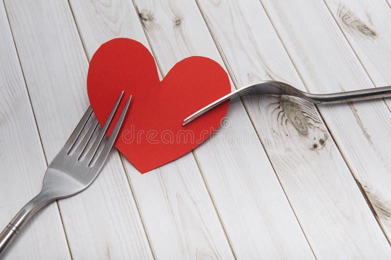 Hart en bestek op een houten achtergrond, heldere raad, de Dag van Valentine ` s stock afbeelding