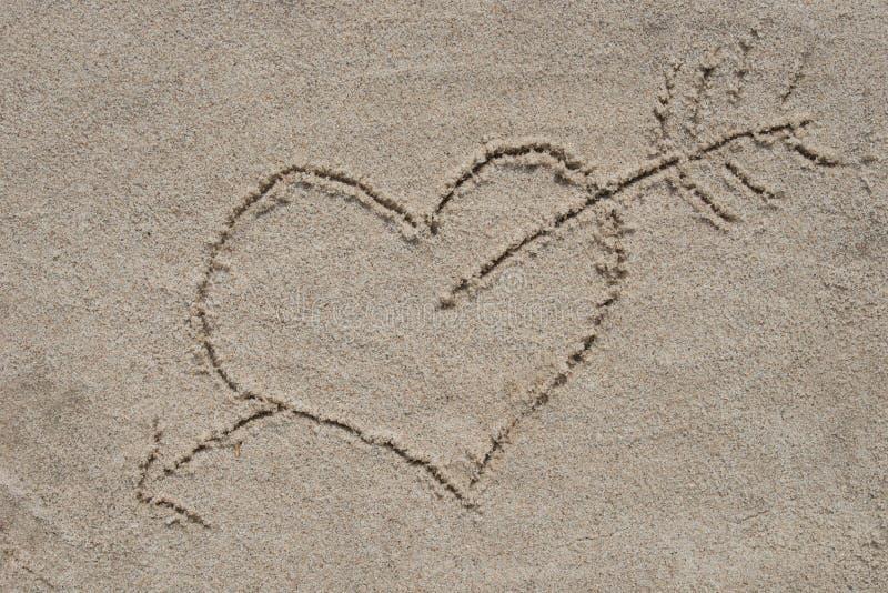 Hart en pijl die op zandzand trekken stock foto's