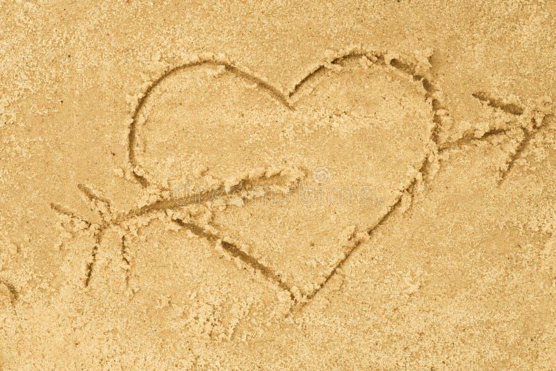 Hart en pijltekening in zand royalty-vrije stock afbeeldingen