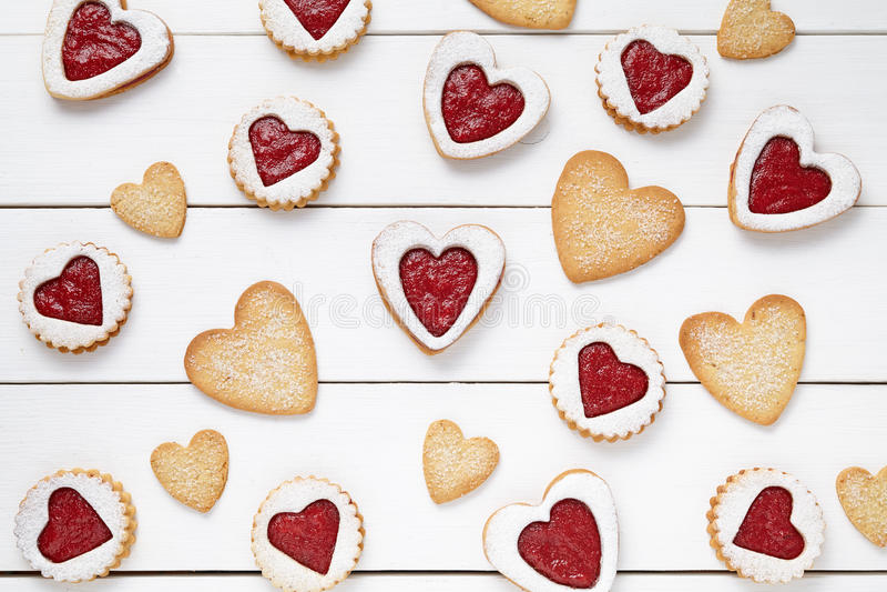 Hart en zandkoekkoekjes met de samenstelling van de jamgift voor Valentijnskaartendag wordt gevormd op uitstekende houten achterg stock foto's