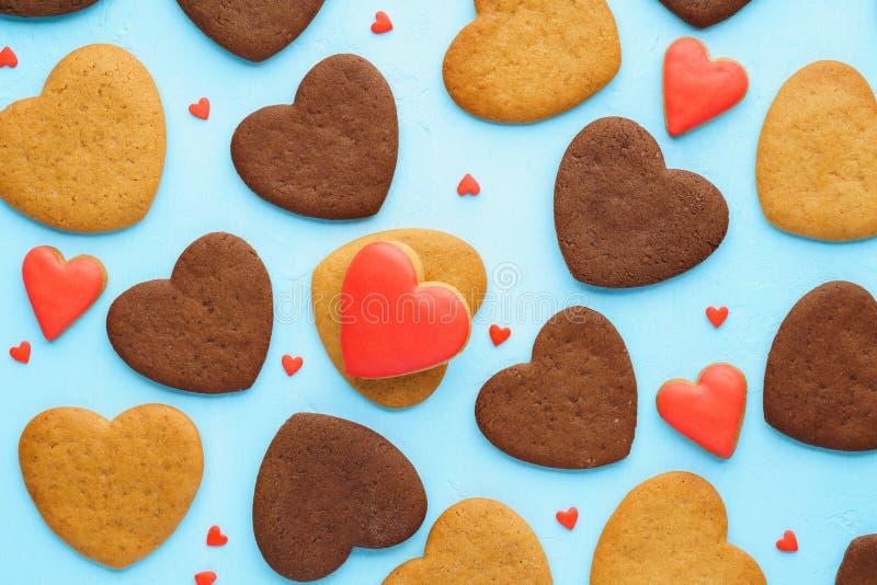 Hart gestalte gegeven koekjes en rode suikergoedachtergrond Valentine' s Dag royalty-vrije stock afbeeldingen