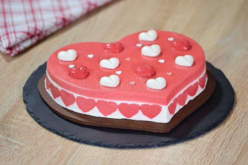 Hart gevormde moussecake Cake in de vorm van een hart op een zwarte plaat stock fotografie