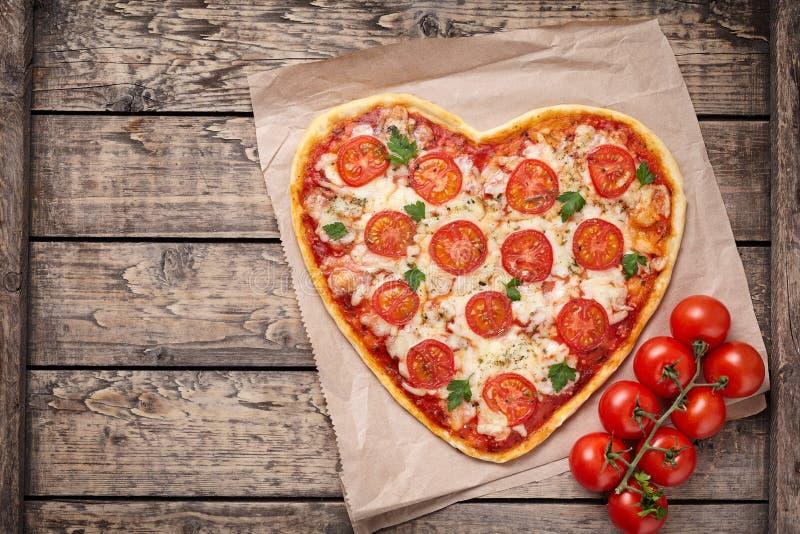 Hart gevormde pizzamargherita met tomaten en stock afbeelding