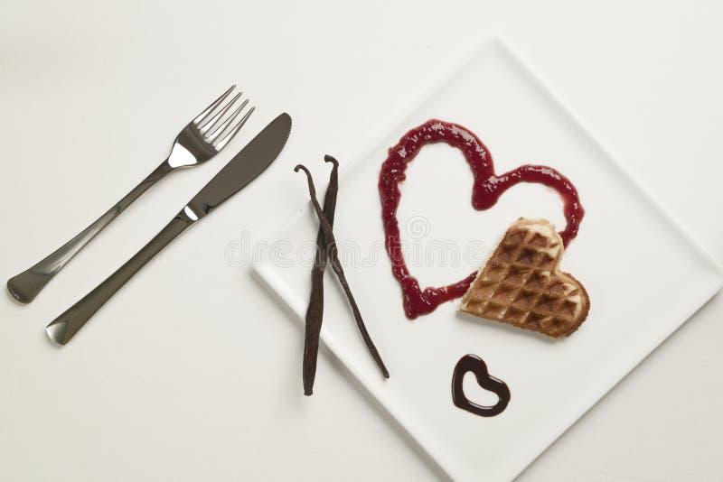 Hart gevormde wafels, marmelade, chocoladesaus, vanillestokken stock foto's