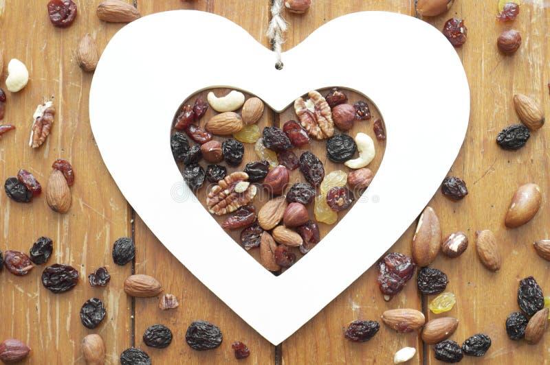 Hart, noten en rozijnen op houten achtergrond stock foto