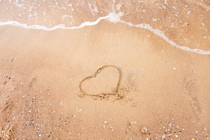 Hart op een zand van strand met de golf van het overzees wordt getrokken die Vrije ruimte voor uw tekst De vakantieconcept van de royalty-vrije stock afbeeldingen