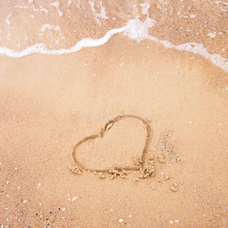 Hart op een zand van strand met de golf van het overzees wordt getrokken die Vrije ruimte voor uw tekst De vakantieconcept van de stock foto