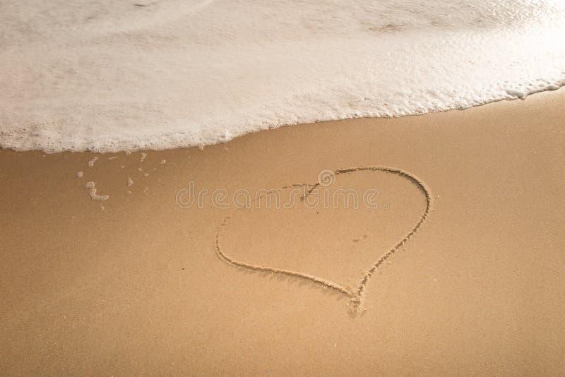Hart op een zand van strand met de golf van de overzeese Romantische liefdeachtergrond die wordt getrokken stock afbeeldingen