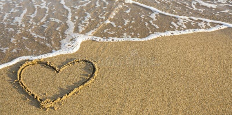 Hart op oceaanstrandzand dat wordt getrokken romantisch royalty-vrije stock fotografie