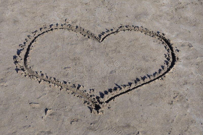 Hart op zand stock afbeelding