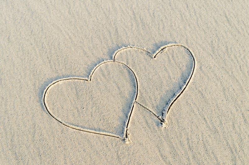 Hart op zand wordt getrokken dat stock foto