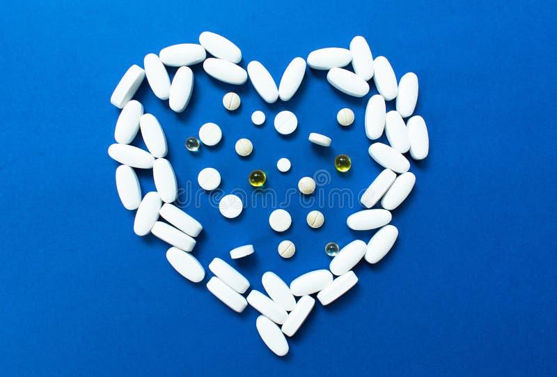 Hart opgemaakte pillen op blauwe achtergrond Concept hartkwaal royalty-vrije stock afbeelding