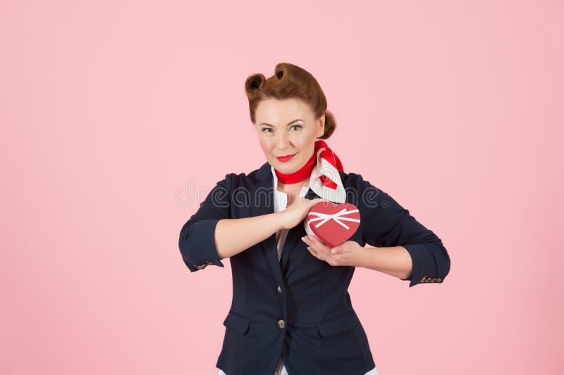Hart rode doos ter beschikking van speld-omhooggaande gestileerde rode haarvrouw Aantrekkelijke dame die haar hart met liefde ver stock afbeelding