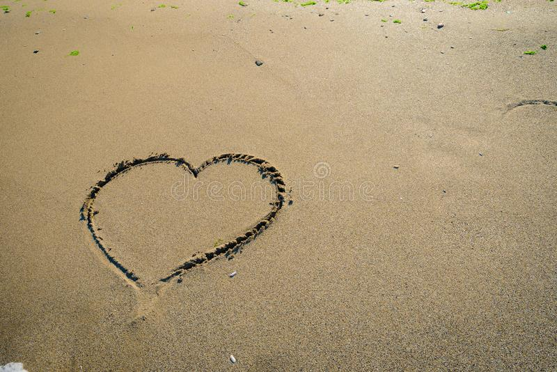 Hart in sand washed by waves stock photo