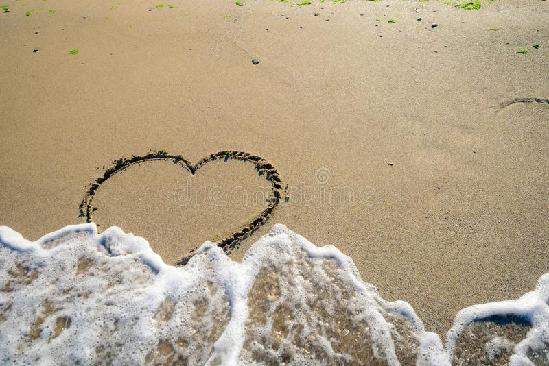 Hart in sand washed by waves royalty free stock image