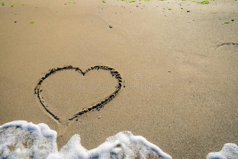Hart in sand washed by waves royalty free stock photo