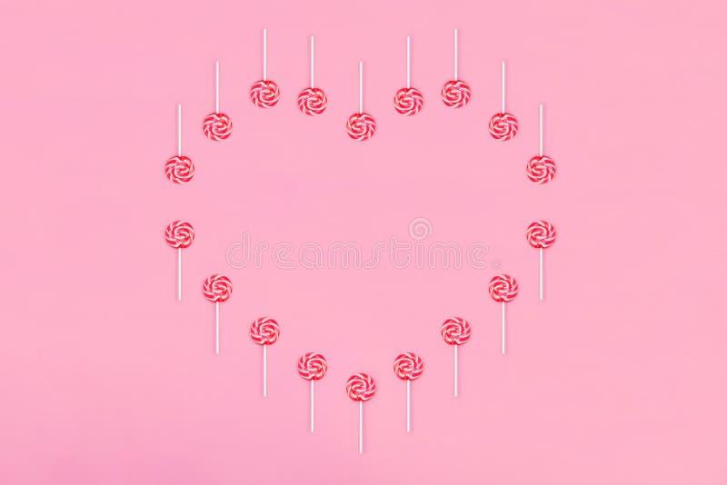 Hart uit lollypopsuikergoed wordt gemaakt op roze achtergrond, exemplaarruimte die De kaart van de de daggroet van de valentijnsk stock foto