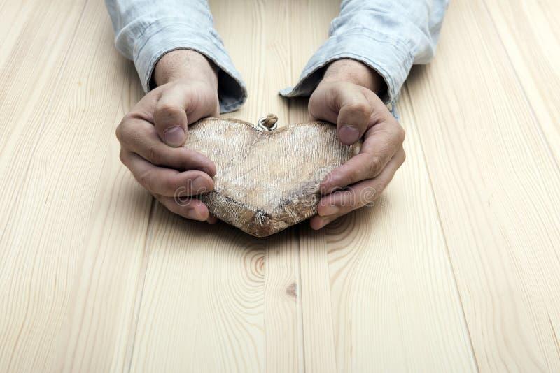 Hart van hout wordt gemaakt dat De handen van mensen houden een hart royalty-vrije stock afbeelding