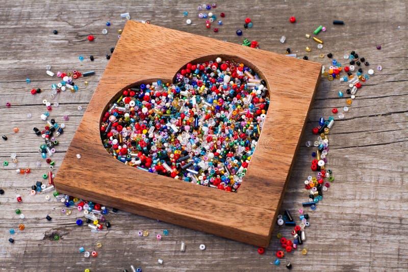 Hart van kleurrijke parels in houten hart-vormige doos stock foto