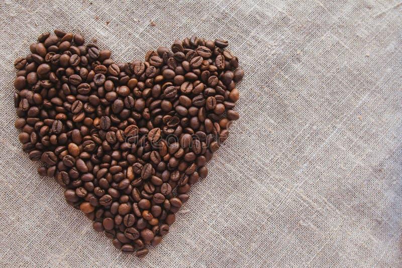 Hart van koffiebonen op linnen hoogste mening stock afbeelding