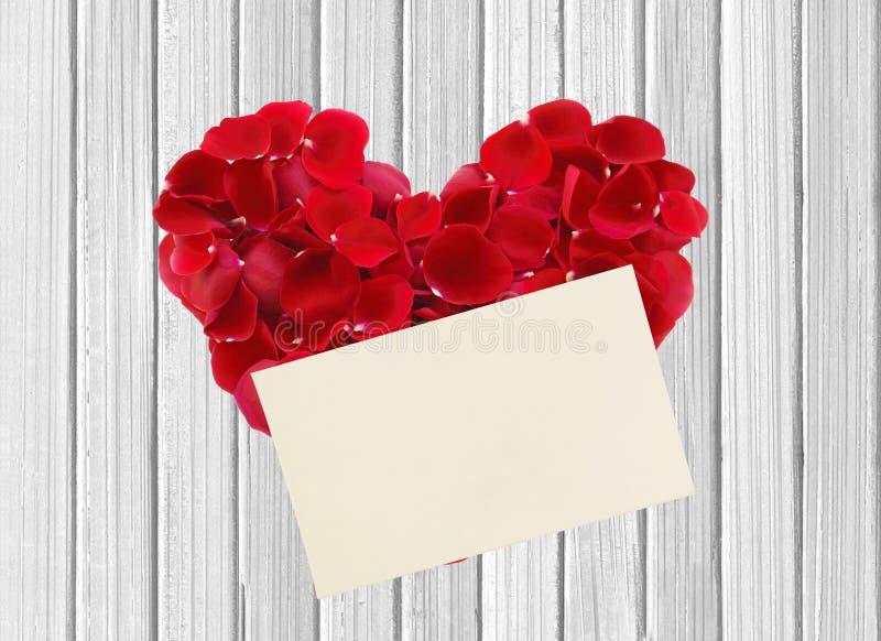 Hart van rode roze bloemblaadjes en document op houten lijst stock foto