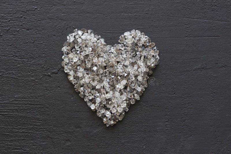 Hart van stenen, liefde Verspreide diamanten op zwarte achtergrond Ruwe diamanten en mijnbouw, het verspreiden zich van natuurlij stock foto's