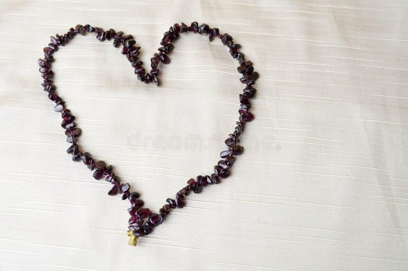 Hart van vrouwelijke mooie parels, halsbanden wordt gemaakt van bruine donkere stenen, amber tegen een achtergrond van beige stof stock afbeeldingen