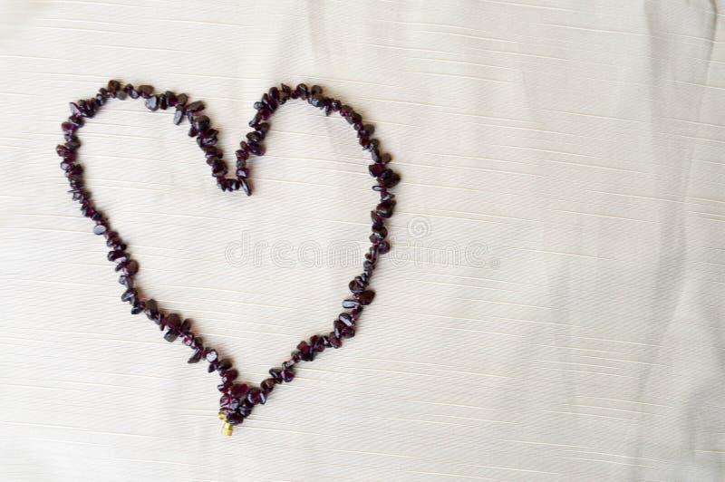 Hart van vrouwelijke mooie parels, halsbanden wordt opgemaakt van bruine donkere stenen, amber tegen een achtergrond van beige st royalty-vrije stock foto's