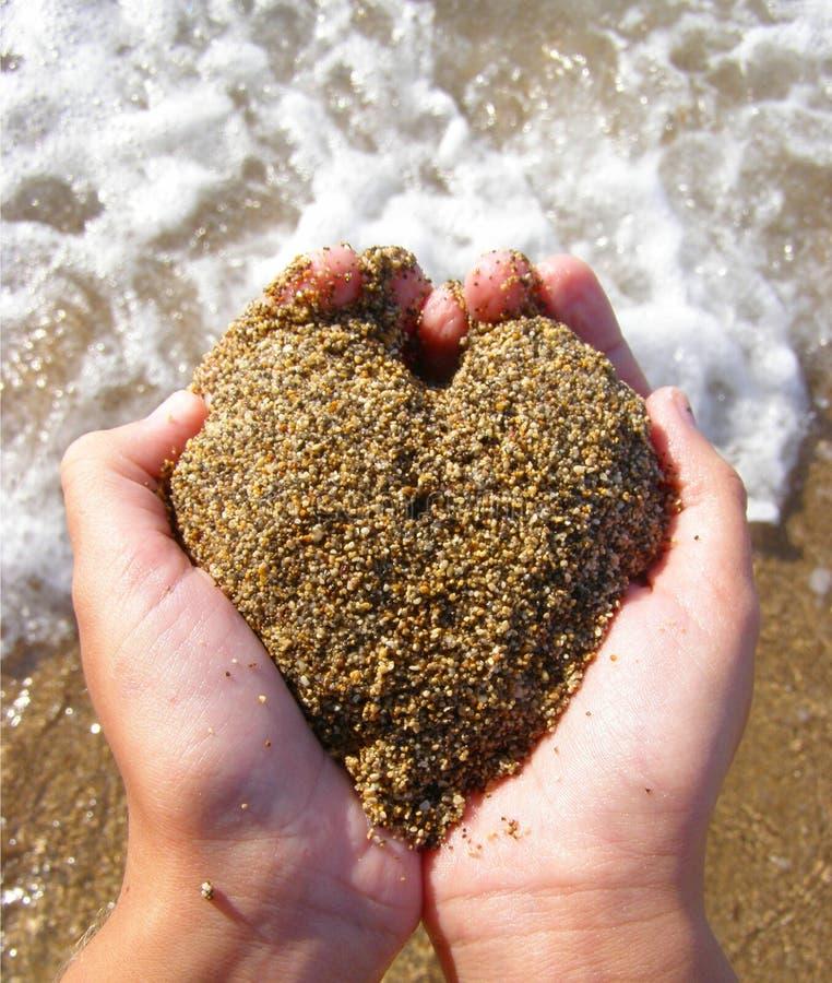 Hart van zand in handen stock foto's