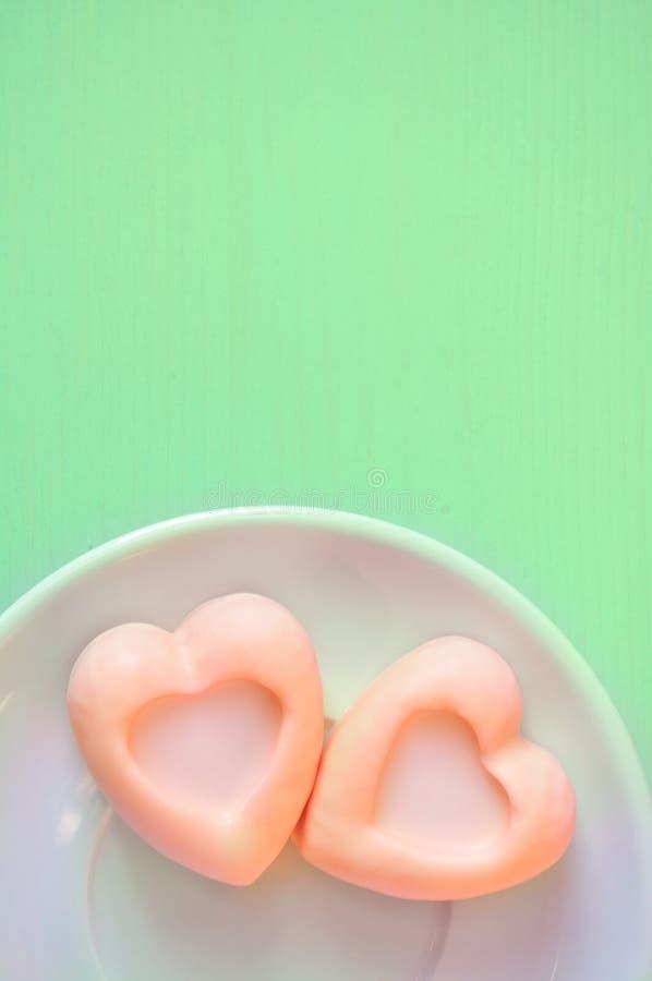 Hart-vormige bleke oranje soufflécakes op de groene houten lijst Selectieve zachte nadruk op de cake en pastelkleurverwerking stock foto