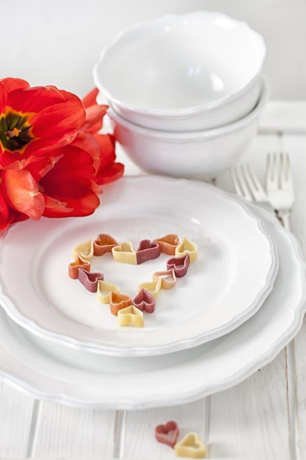 Hart-vormige deegwaren en tulpen stock foto