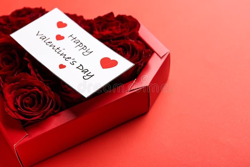 Hart-vormige doos met roze knoppen en kaart op kleurenachtergrond De Viering van de valentijnskaartendag royalty-vrije stock afbeeldingen